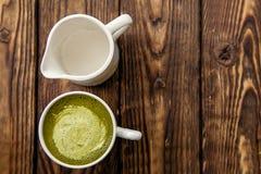 Tasse de latte chaud de thé vert de matcha et tasse de lait sur le fond en bois images libres de droits