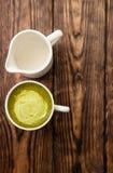 Tasse de latte chaud de thé vert de matcha et tasse de lait sur le fond en bois photographie stock libre de droits
