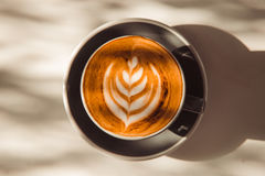 Tasse de latte d'art ou de café de cappuccino sur la table avec la lumière du soleil Photo stock