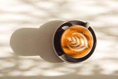 Tasse de latte d'art ou de café de cappuccino sur la table avec la lumière du soleil Image stock