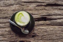 Tasse de latte de matcha contre la vieille table en bois images stock