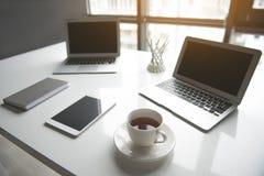 Tasse de liquide et d'appareils sur la table Photos libres de droits