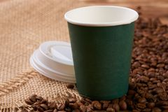 Tasse de Livre vert et grains de café sur la table en bois Image stock