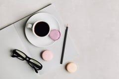 Tasse de matin de café, de carnet vide, de crayon, de verres et de macaron de gâteau sur la vue aérienne de bureau gris Belle con Image stock