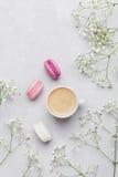 Tasse de matin de café, de macaron de gâteau et de fleur sur le fond clair d'en haut Beau style de configuration d'appartement de Photographie stock