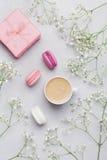 Tasse de matin de café, macaron de gâteau, cadeau ou boîte et fleur actuelles sur la table grise d'en haut Beau style de configur Photographie stock