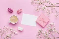 Tasse de matin de café, macaron de gâteau, cadeau ou boîte et fleur actuelles sur la table rose d'en haut Belle configuration d'a Images stock