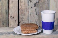 Tasse de pain et de café sur le bureau en bois Images libres de droits