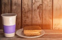 Tasse de pain et de café sur le bureau en bois Image libre de droits