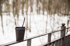 Tasse de papier avec des supports de caf? sur une balustrade en m?tal sur le pont images stock