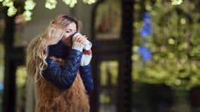 Tasse de papier chaude potable de chauffage femelle de café extérieure au fond jaune de lumières de bokeh d'éclat banque de vidéos