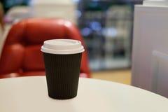 Tasse de papier de café chaud avec le fond rouge de chaise Photographie stock libre de droits