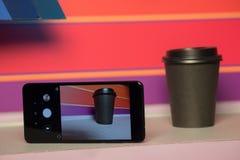 Tasse de papier noire avec le couvercle en plastique café ou traiteur sur un fond violet et rose verre brutal avec le téléphone p image stock