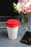 Tasse de papier potable de café près d'ordinateur portable Photographie stock libre de droits
