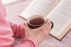 Tasse de participation de femme de livre de thé et de lecture à la maison image libre de droits