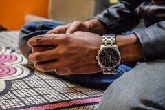 Tasse de participation de main et utiliser une montre attrayante dans le poignet photo stock