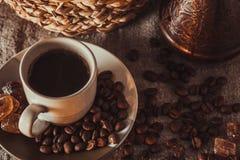 Tasse de petit déjeuner de café sur le textile avec les haricots, le sucre foncé de sucrerie, les pots, le panier et le gâteau Photo libre de droits