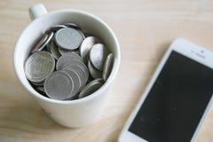 Tasse de pièce de monnaie et de téléphone Images stock