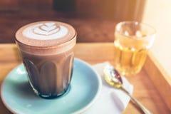 Tasse de plan rapproché d'art chaud de cacao sur la soucoupe avec la cuillère et le thé Photo stock