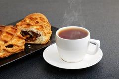 Tasse de plan rapproché de thé et de strudel avec les pommes et la cannelle Photographie stock