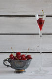 Tasse de porcelaine avec des cerises et des glas d'eau-de-vie fine Photographie stock