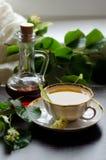 Tasse de porcelaine de thé et de sirop d'érable de tilleul sur un fond de bois foncé Images stock
