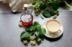 Tasse de porcelaine de thé et de sirop d'érable de tilleul sur un fond de bois foncé Image stock