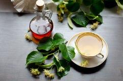 Tasse de porcelaine de thé et de sirop d'érable de tilleul sur un fond de bois foncé Photographie stock