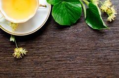 Tasse de porcelaine de thé et de sirop d'érable de tilleul sur un fond de bois foncé Photo libre de droits