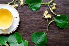 Tasse de porcelaine de thé et de sirop d'érable de tilleul sur un fond de bois foncé Photos stock