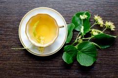 Tasse de porcelaine de thé et de sirop d'érable de tilleul sur un fond de bois foncé Image libre de droits