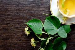 Tasse de porcelaine de thé et de sirop d'érable de tilleul sur un fond de bois foncé Photo stock