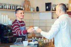 Tasse de portion de barman de café au client au compteur dans le petit café images stock