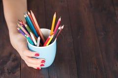 Tasse de prise de femme avec beaucoup crayon de couleur photographie stock