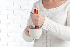 Tasse de prise de femme avec beaucoup crayon de couleur image libre de droits