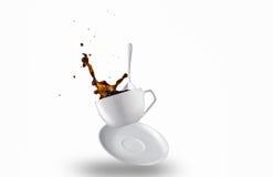 Tasse de renverser le café noir créant une éclaboussure Images stock