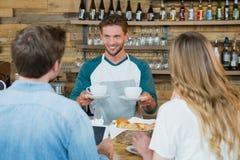Tasse de serveur de café servante de sourire aux clients au compteur image stock