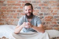 Tasse de sourire de lit de hippie de chaleur de boissons de matin photo stock