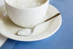 Tasse de sucre raffiné sur le fond bleu blanc photographie stock libre de droits