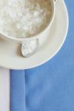 Tasse de sucre raffiné sur le fond bleu blanc images stock