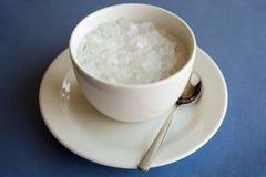 Tasse de sucre raffiné sur le fond bleu blanc image libre de droits