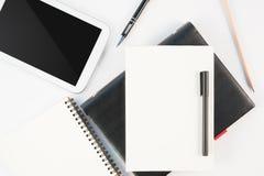 Tasse de téléphone de comprimé de café et de carnet chauds de journal intime sur le fond blanc Image libre de droits