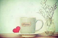 Tasse de tasse de café avec l'étiquette heureuse de mot de shapeand rouge de coeur sur en bois Photographie stock libre de droits