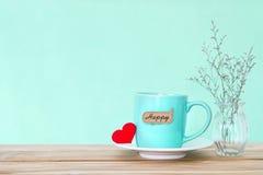 Tasse de tasse de café avec l'étiquette heureuse de mot de shapeand rouge de coeur sur en bois Photographie stock