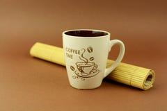 Tasse de temps de café avec le fond de brun de placemat Photographie stock libre de droits
