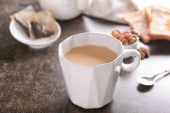 Tasse de thé au lait aromatique sur la table images stock