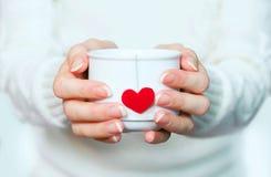 Tasse de thé avec amour dans des mains Images libres de droits