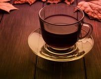 Tasse de thé avec des feuilles sur un fond en bois noir Instagram Photos stock