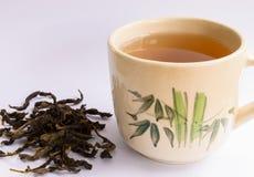 Tasse de thé avec la feuille de thé Images stock