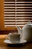 Tasse de thé avec la théière dans la perspective des abat-jour Image libre de droits